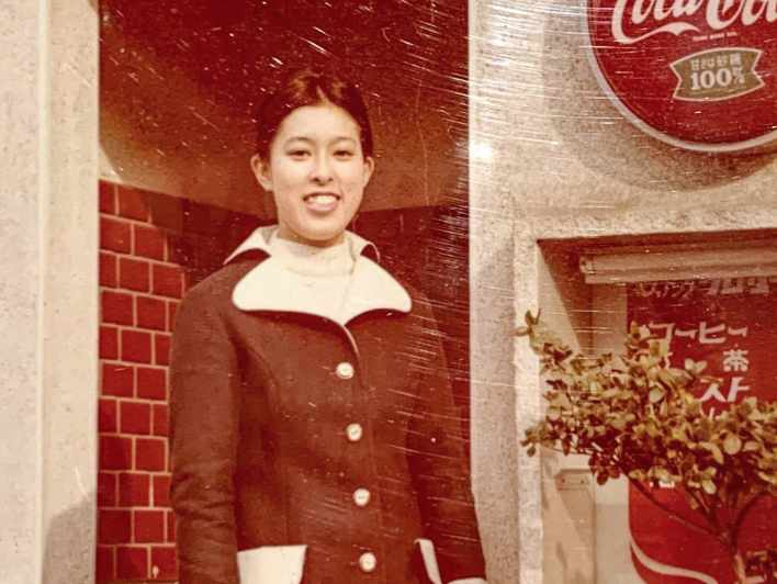 レストラン ニューグローリーの前身である喫茶店をバッグに当時の制服を着た女将さんの写真です