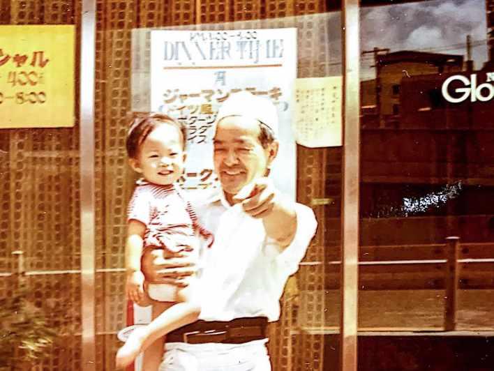 お店をバックに初代マスターが子供を抱っこしてカメラに向かって指を指している写真です